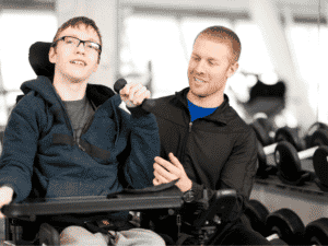 Professional trainer assists handicapped boy in wheelchair with lifting a hand weight