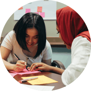 Teacher helping student at desk with written assignment