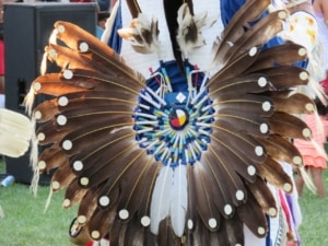 Close up of Indegenous regalia of eagle feathers on the back of a dancer