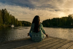 Girl sitting meditating looking out at water
