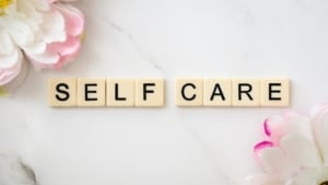 Scrabble blocks spelling Self Care surrounded by flower petals.