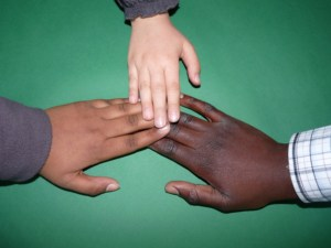 Three hands of different skin colors reaching out and touching fingertips