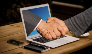 A hand coming out of a laptop screen to shake hands with someone at a desk