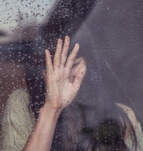Sad girl with her forehead resting on back of palm that is pressed against a glass window pane covered in raindrops