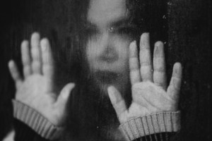 Sad girl looking out window on rainy day with hands against glass