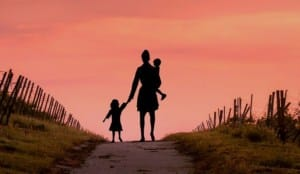 Siloutte of backs of a mother carrying toddler and holding hands with little girl walking into the sunset