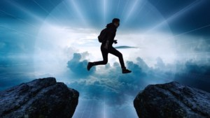 Boy jumping through air from one cliff to another