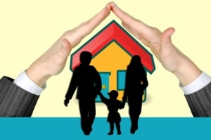 Hands sheltering a graphic of a house with a family infront