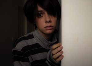 A a younger person about age ten standing by a door with a look of fear or distress