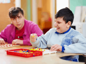 2 developmentally handicapped youth at table working on puzzles and peg boards