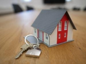 Tiny modle house beside keys on table