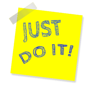 Yellow sticky note with the words Just Do It and an exclamation mark written on with felt pen