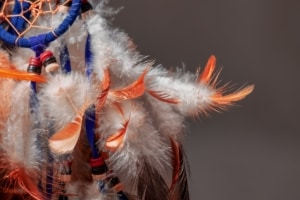 A dream catcher with white and orange feathers
