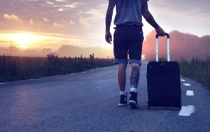 young man pulling suitcase walking down the road into the sunset