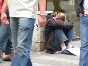 Teen girl sitting on sidewalk with head down