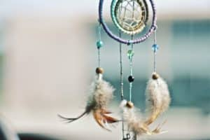 an indigenous dream catcher with beads and feathers